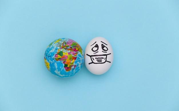 파란색 배경에 의료 마스크와 지구본의 달걀 얼굴. 코로나 19 감염병 세계적 유행. 평면도