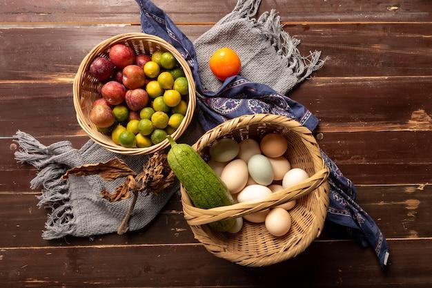 かごの中の卵やその他の果物や野菜は木目調のテーブルの上にあります