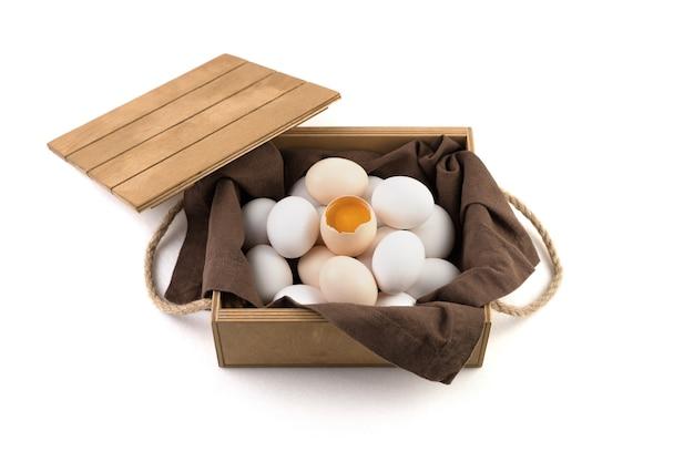 Яйца бело-коричневые с разбитым яйцом в центре, в котором виден свежий желток.