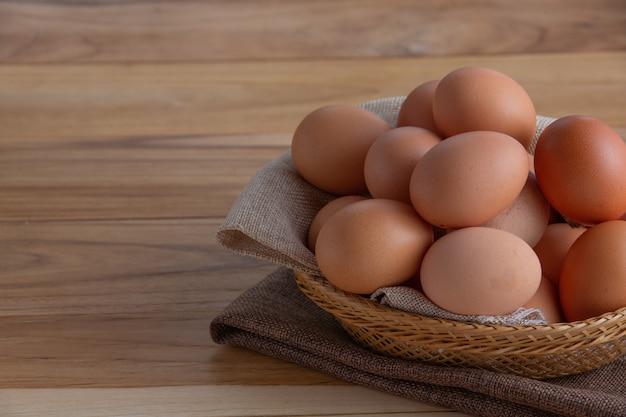 Яйца в корзине размещены на деревянном полу.