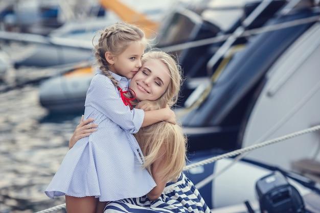 Старшая сестра и младшие сестры и брат в морском стиле на фоне катеров и яхт. идея и концепция дружба, отпуск, отпуск, семья