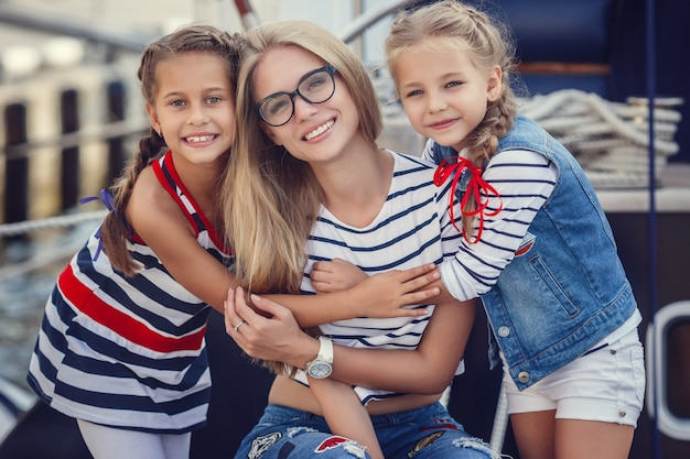 Старшая сестра и младшие сестры и брат в морском стиле на фоне катеров и яхт