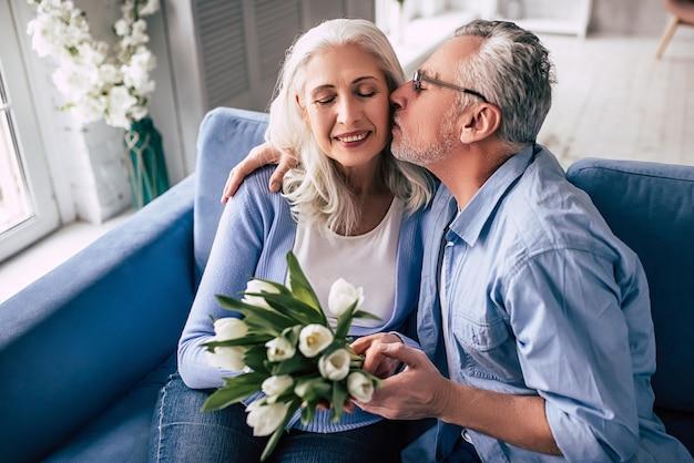Пожилой мужчина и женщина с цветами целуются
