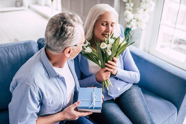 Пожилой мужчина делает подарок женщине с цветами