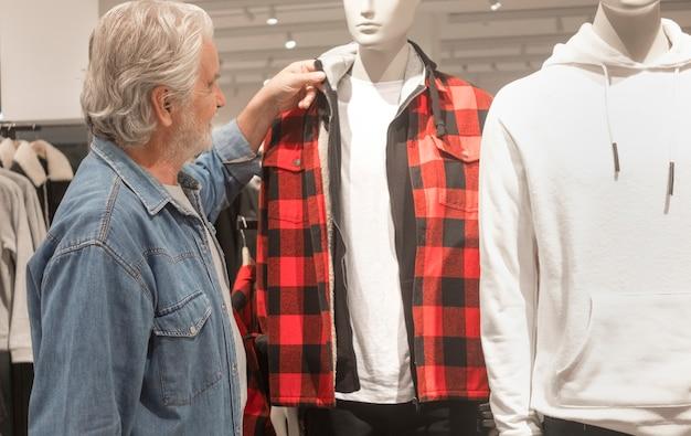 あごひげと白い髪の老人は、マネキンに表示されているオブジェクトを見ます