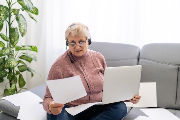 Пожилая женщина пишет на компьютере.