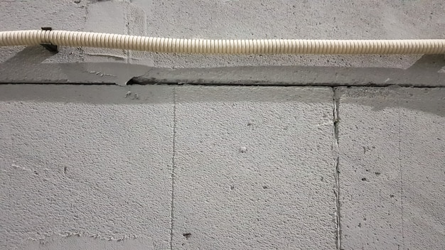 Электрокабель прокладывается в защитной гофре над стеной. по стене проложены электрические провода для подключения розеток и выключателей.