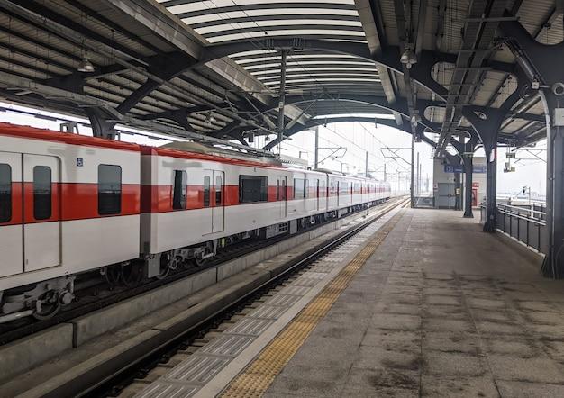 전철은 퇴근 시간에 역에서 교외 지역으로 출발하고, 복사 공간이 있는 전면 모습입니다.