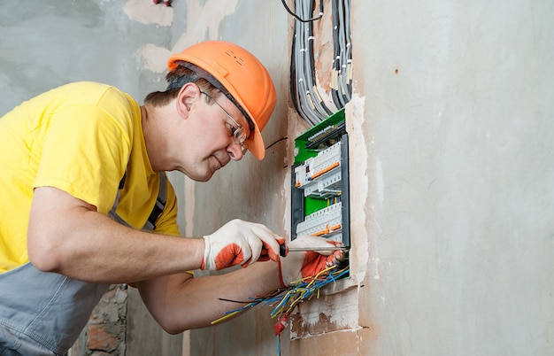 Электрик устанавливает предохранители.