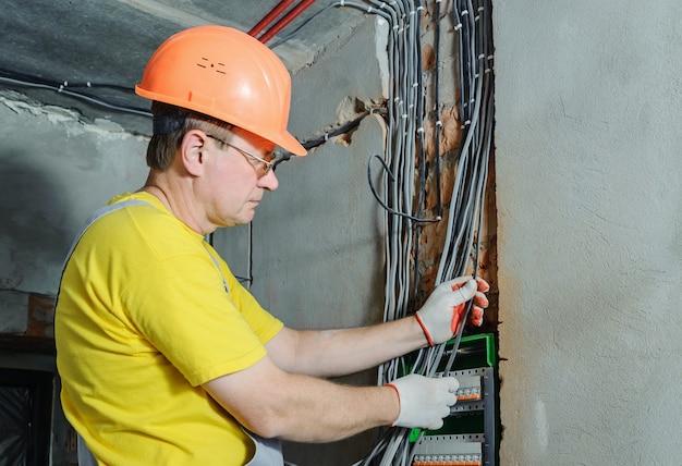 Электрик устанавливает электрические провода в коммутационном блоке предохранителей