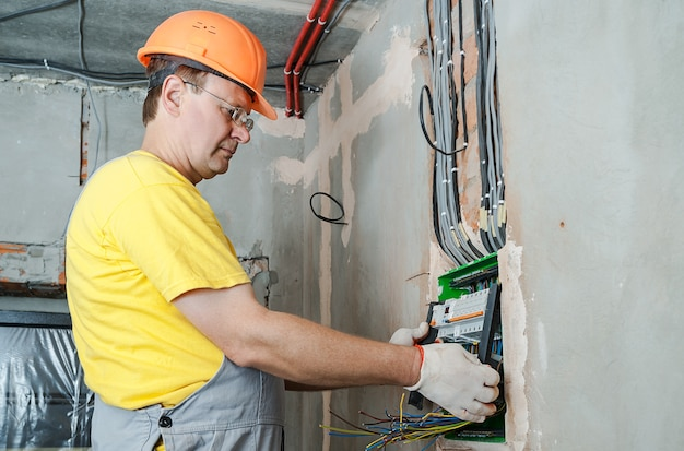 Электрик устанавливает предохранители в распределительной коробке