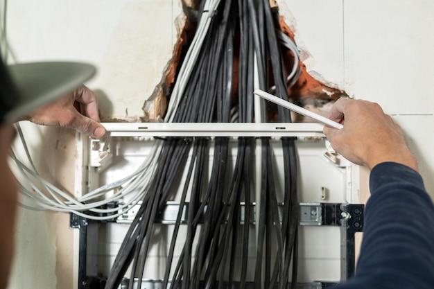 電気技師は電気パネルを設置し、ワイヤーを準備します
