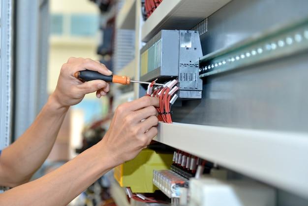 電気技師は電気ケーブルのワイヤーを接続しています。エンジニアによるメンテナンスとシステム制御の修正。