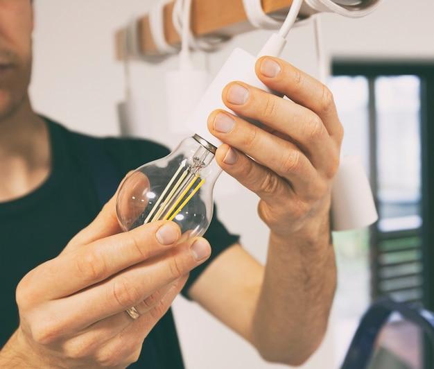전기 기사가 led 전구를 샹들리에에 설치하고 있습니다.