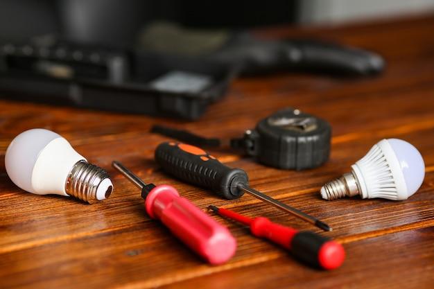 전기 기사의 도구가 탁자 위에 있습니다. 작업장에서 장비 수리, 램프, 스크루 드라이버, 장갑 교체 과정. 고품질 사진