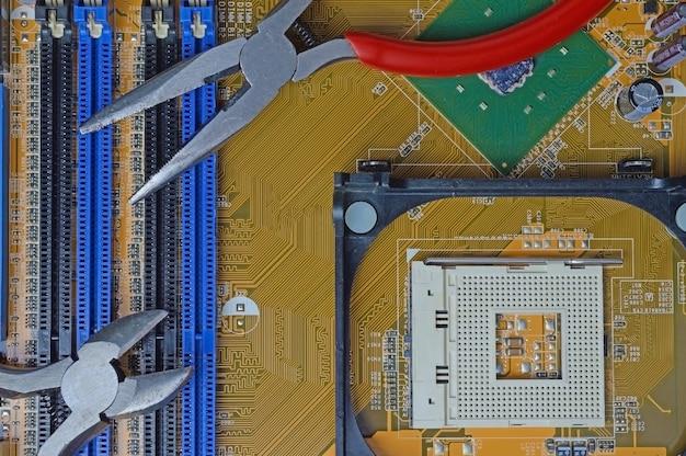 Инструмент для ремонта электроники лежит на материнской плате от компьютера. крупный план.