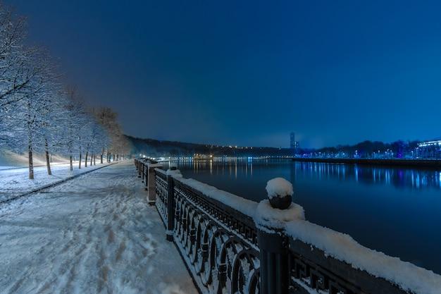 モスクワ川の堤防は夜の冬です。歩道や木々は新雪で覆われています。反対側の土手にあるイルミネーションライト。カラフルな街並み。