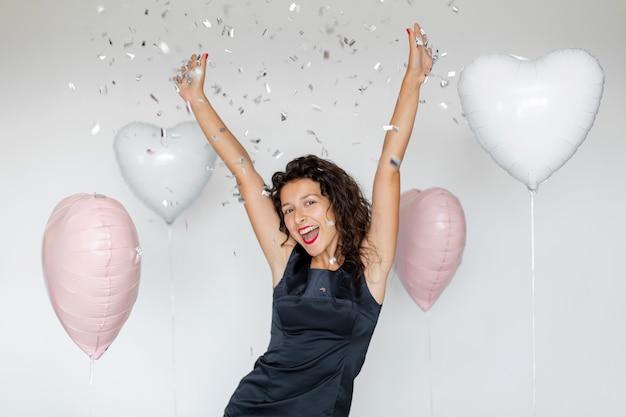 Эмоция успеха. счастливая сексуальная девушка брюнет, наслаждаясь празднованием с конфетти и сердечными воздушными шарами на белом фоне.