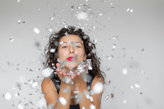 Эмоция успеха. счастливая сексуальная девушка брюнетка наслаждается празднованием с конфетти на белом фоне.