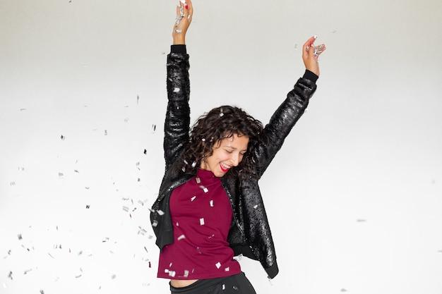 Эмоция успеха. счастливая сексуальная брюнетка девушка наслаждается празднованием с конфетти на белом фоне