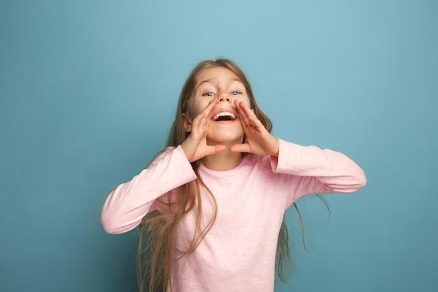 감정적 인 금발의 십대 소녀는 행복해 보이고 비명을 지르고 있습니다. 스튜디오 촬영