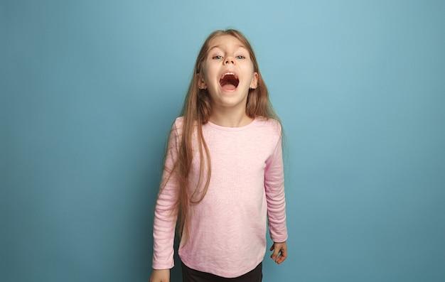 感情的な金髪の十代の少女は、幸せそうな表情と悲鳴を上げています。スタジオ撮影
