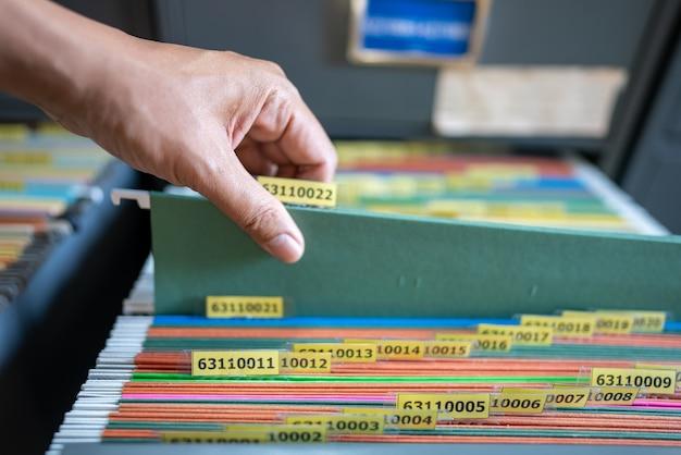 従業員の手は、ファイリングキャビネットで書類を探していました。