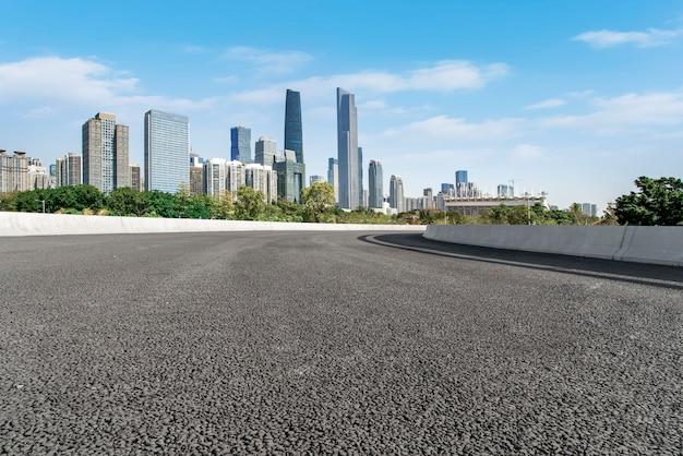 空のアスファルト道路は、中国の都市の近代的な商業ビルに沿って建設されています。