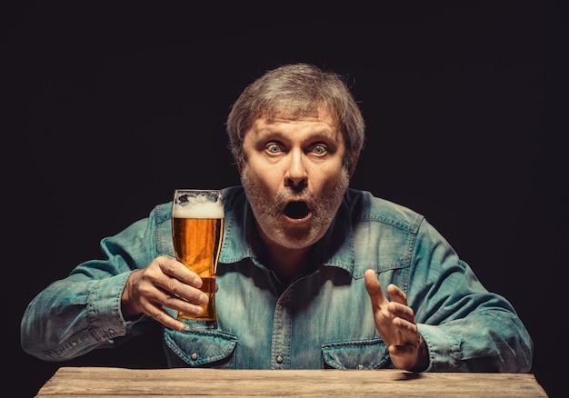 ビールのグラスを持つ魅惑的で感情的なファン