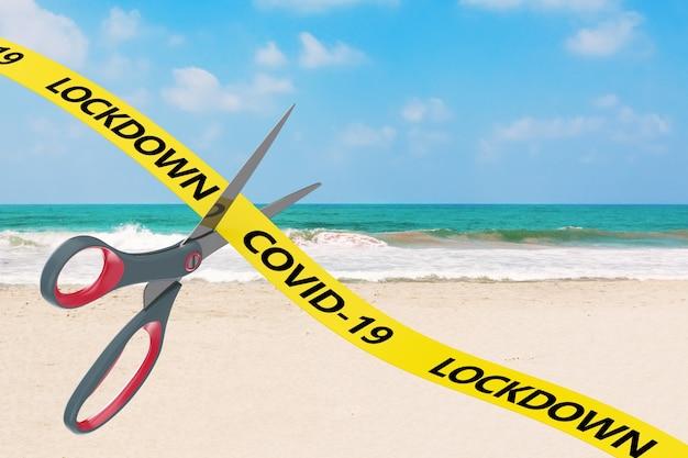잠금 개념의 끝. 가위는 바다 해변 배경에 covid-19 잠금 표시가 있는 노란 리본을 잘라냅니다. 3d 렌더링