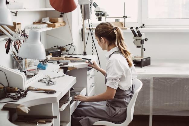 그녀에 앉아 젊은 여성 보석상의 작업 일 측면보기의 끝