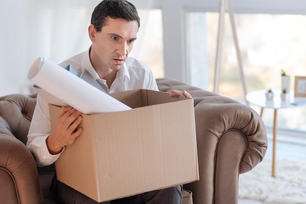 Конец. молодой элегантный серьезный мужчина выглядит потрясенным, сидя в кресле с коробкой личных вещей на коленях после потери любимой интересной работы