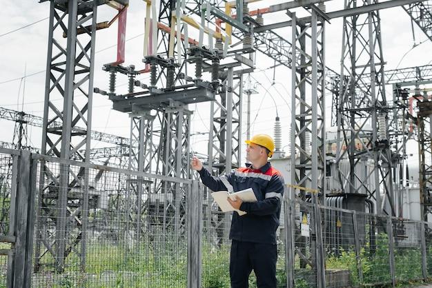 Инженер-энергетик осматривает оборудование подстанции. энергетика. промышленность.
