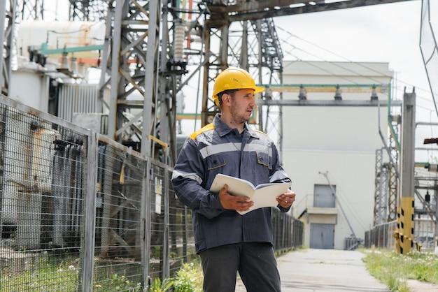 Инженер-энергетик осматривает оборудование подстанции.