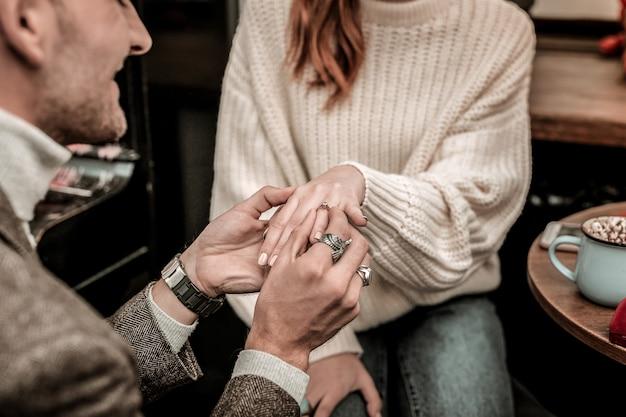 Помолвка. мужчина надевает кольцо на палец партнера