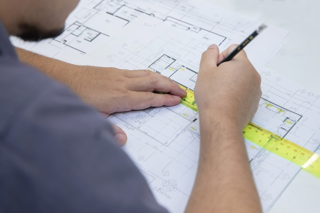 建築プロジェクトの間取り図に線を引くエンジニア