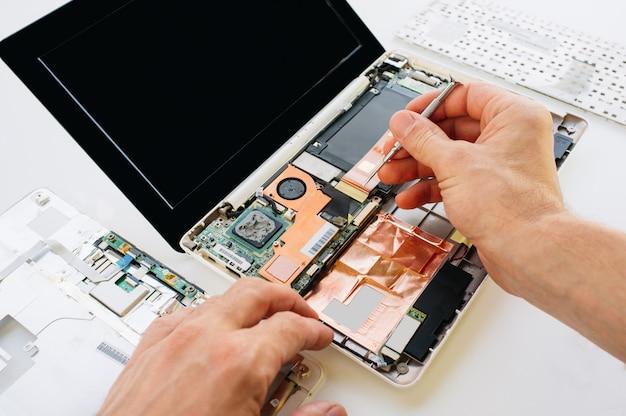 Инженер ремонтирует ноутбук и материнскую плату