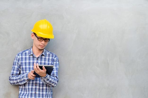 Инженер стоял на цементном фоне и смотрел на планшет. инженеры используют таблетки.