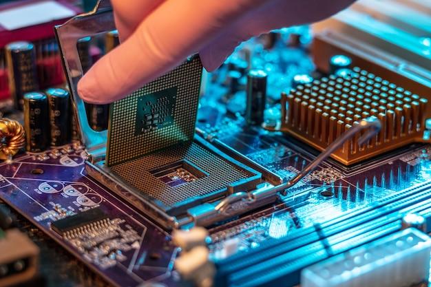 Рука инженеров в перчатке держит чип процессора на фоне материнской платы.