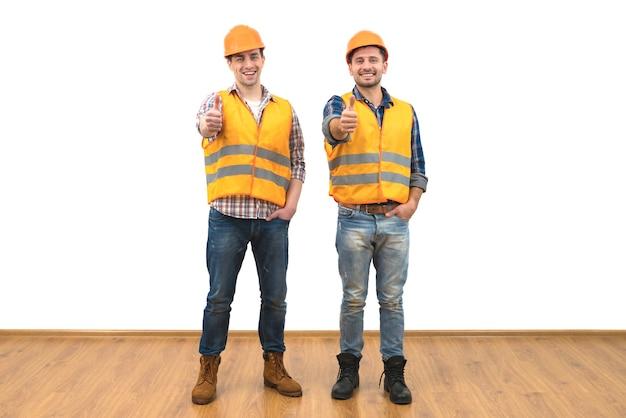 Инженеры поднимают палец вверх на белом фоне стены