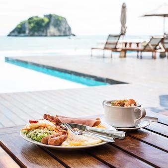 Английский завтрак состоит из яичницы, бекона, колбасы и зеленого салата, а также тайского рисового супа с креветками на фоне пляжа в таиланде.