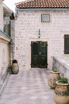 家の入り口は、大きな鉢のある庭を通る火格子のある閉じた金属製のドアです。