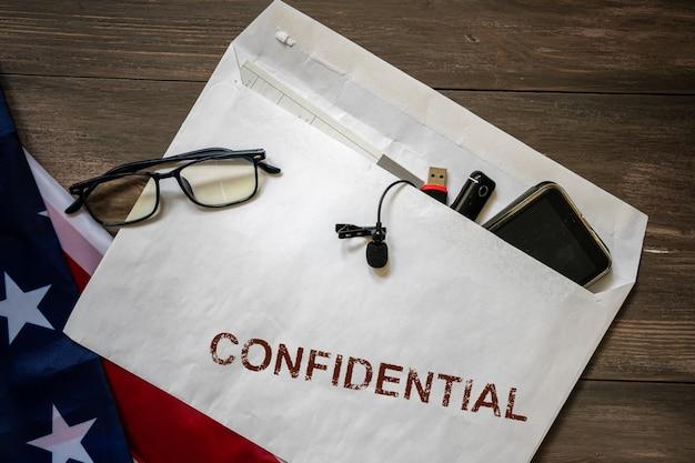 書類の入った封筒と印鑑の電話はテーブルの上で秘密です。スパイ活動と産業セキュリティの概念。