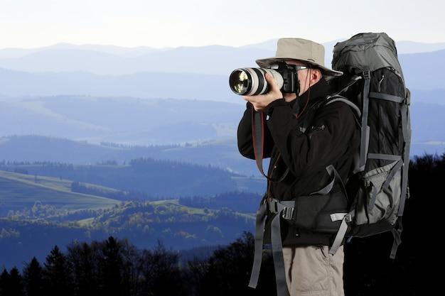 장비를 갖춘 여행자 사진 작가가 자연 사진을 찍습니다.
