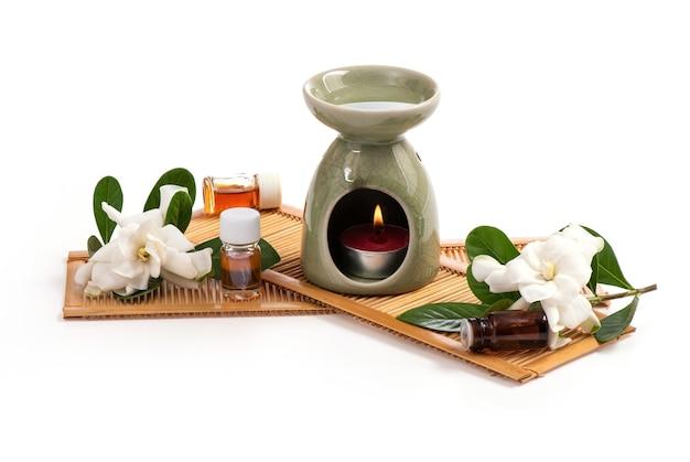 エッセンシャルオイルバーナーとケープジャスミンの花は白の上に置かれます。