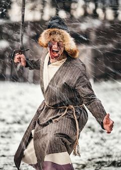 剣で戦う、油を塗った顔をした帽子をかぶった若い戦士の邪悪な感情。冬の戦い