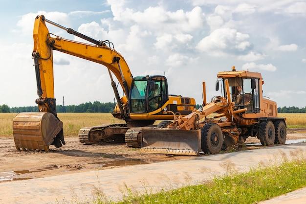 Экскаватор и грейдер стоят бок о бок на фоне голубого неба. тяжелая строительная землеройная техника. строительство дорог и подземных коммуникаций. строительная промышленность.