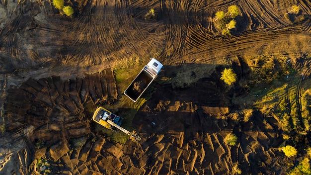 Экскаватор удаляет почву из почвы и загружает ее в грузовик. вмешательство человека разрушает естественную экосистему.