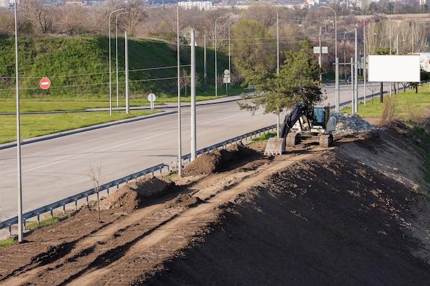 Экскаватор укрепляет склоны на обочине дороги. ремонт дорог.