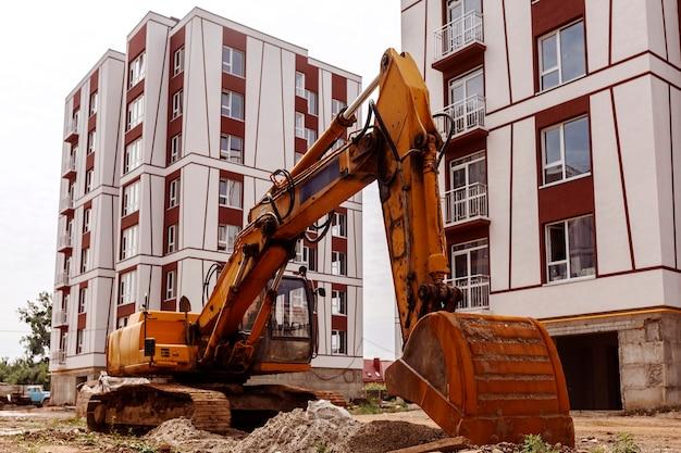 굴착기는 완성된 집의 배경에 대해 건설 현장에서 작동합니다